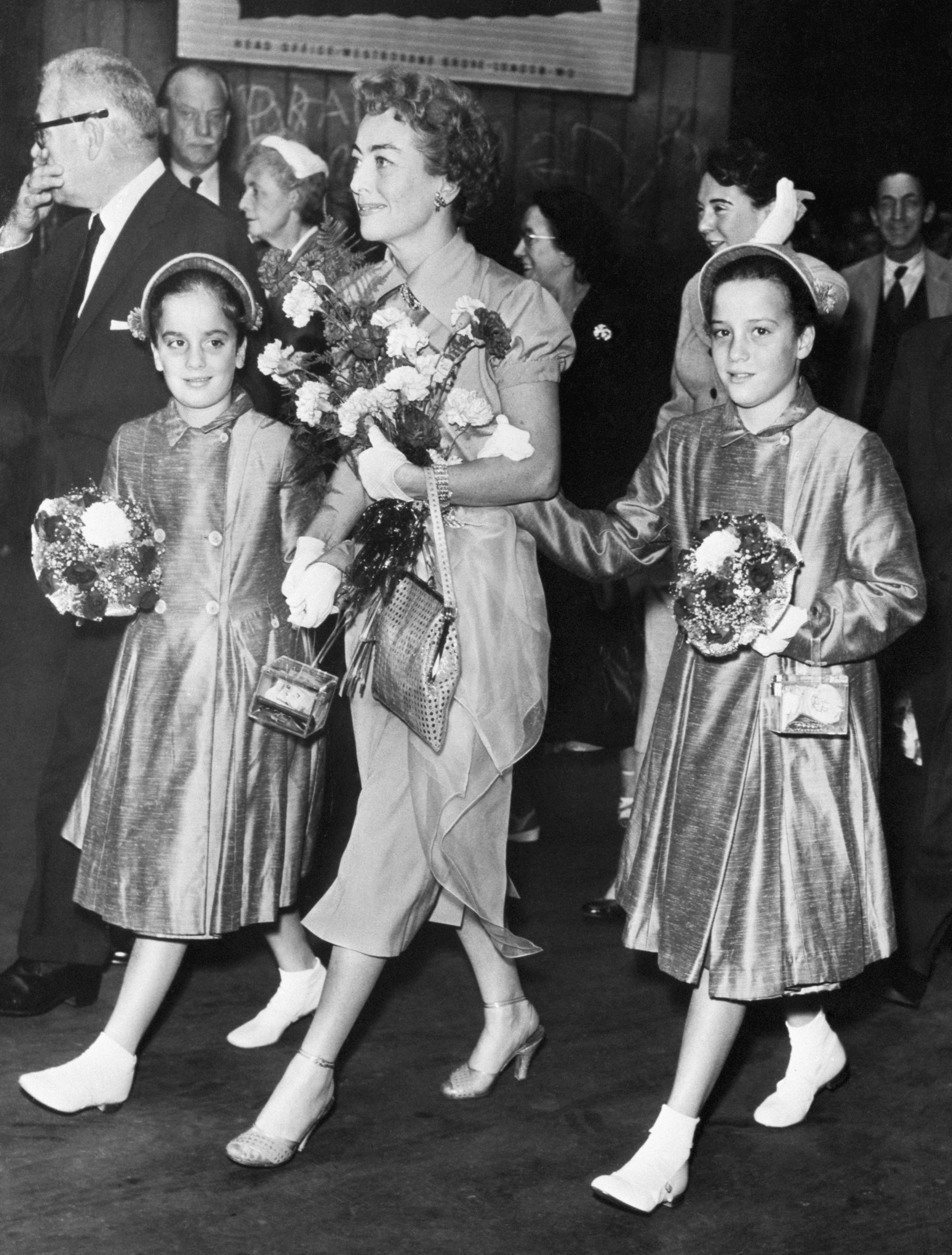 Hollywood actress Joan Crawford strides along the platform of London's Paddington Station with her adopted twin daughters, Cynthia (right) and Cathy, 8/3/56-London, England:   Source: Getty Images