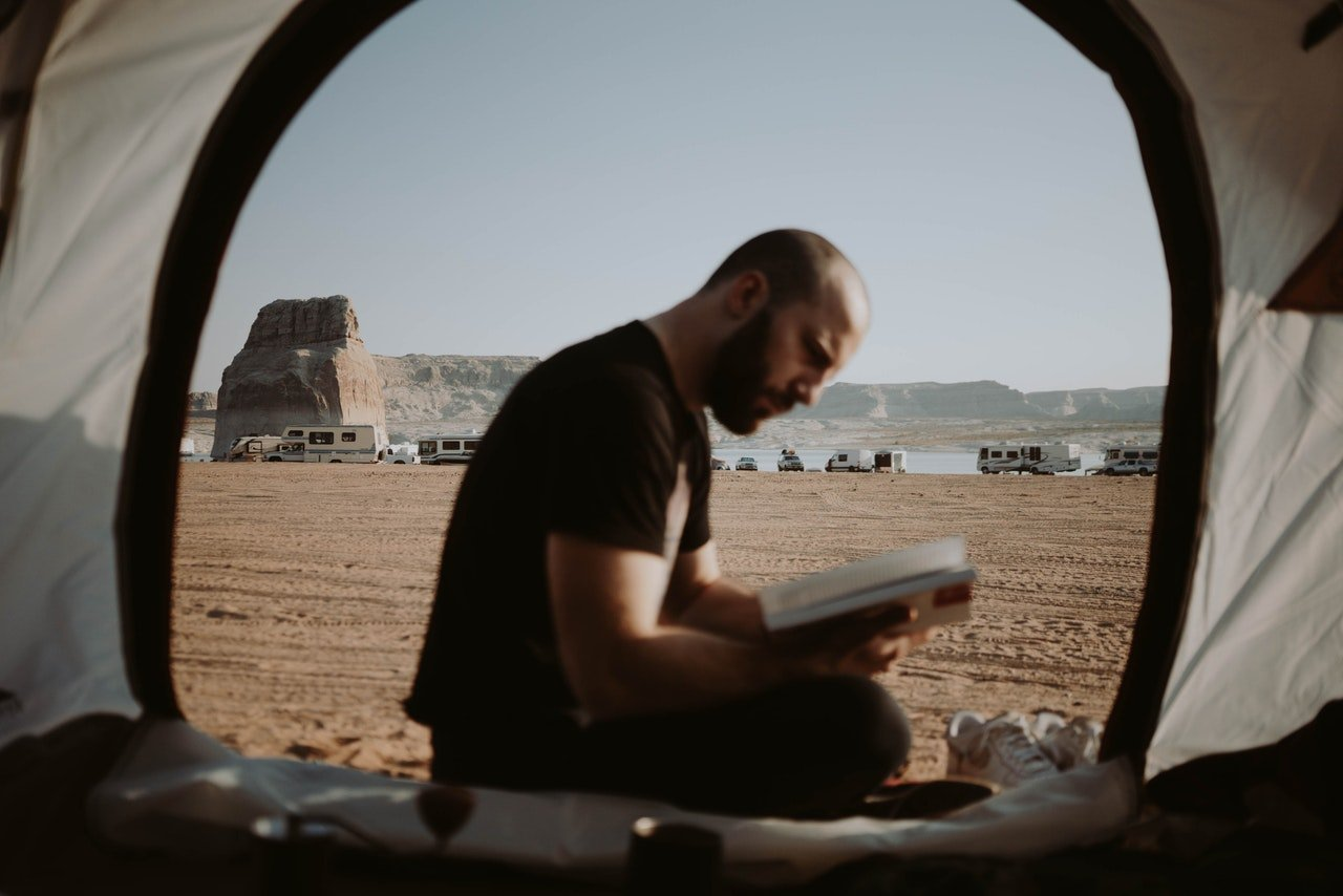 Photo of man reading a book in a tent | Photo: Pexels