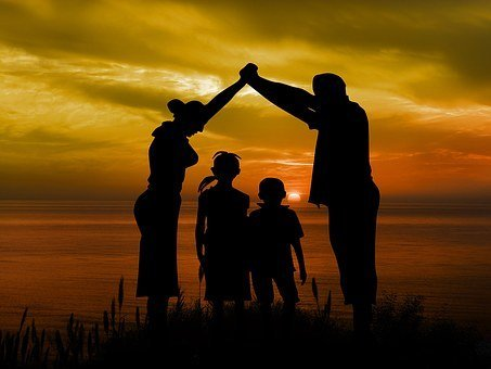 A silhouette of a happy family of four. | Photo: Pixabay