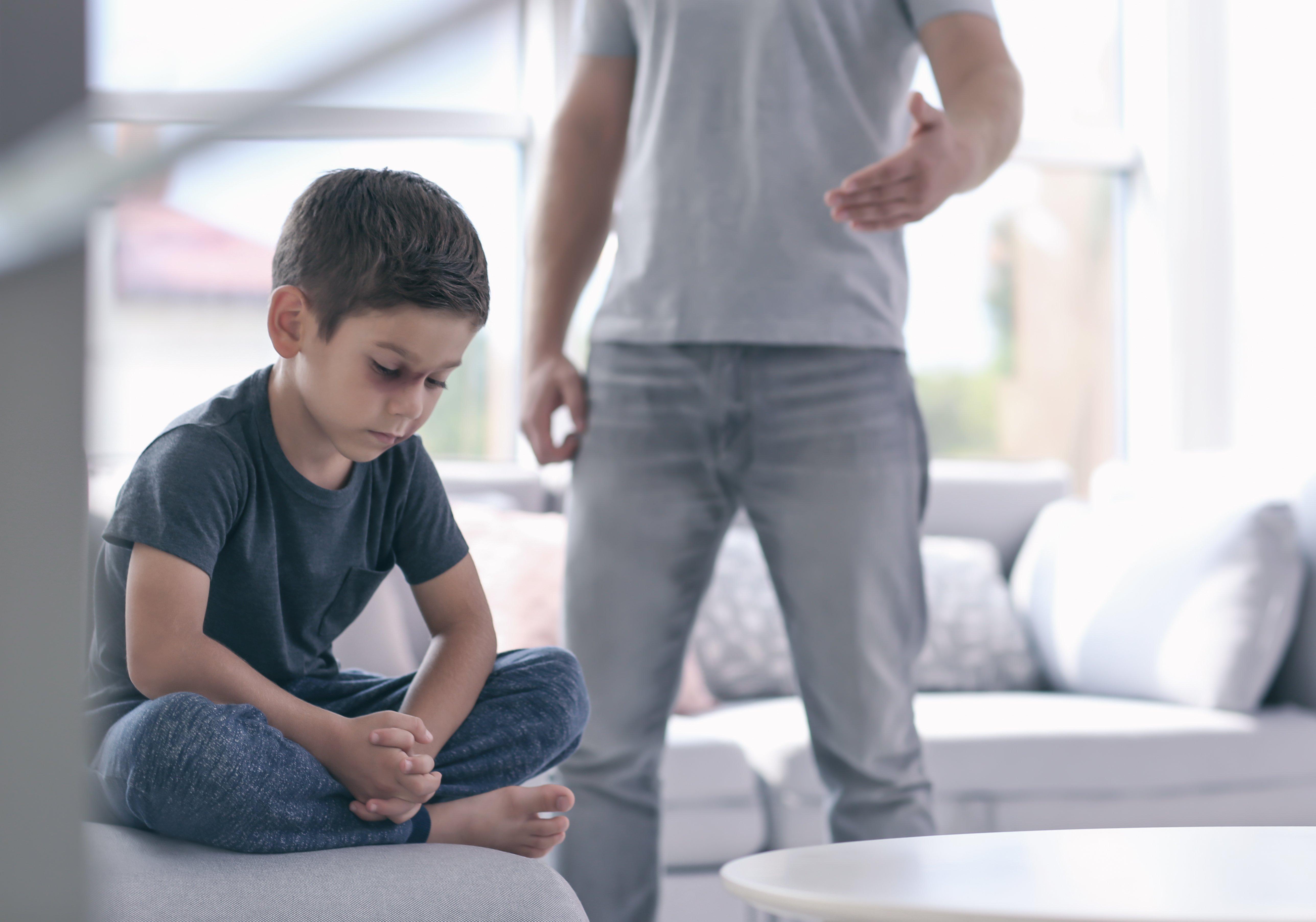 Un homme réprimande un petit garçon | Photo : Shutterstock