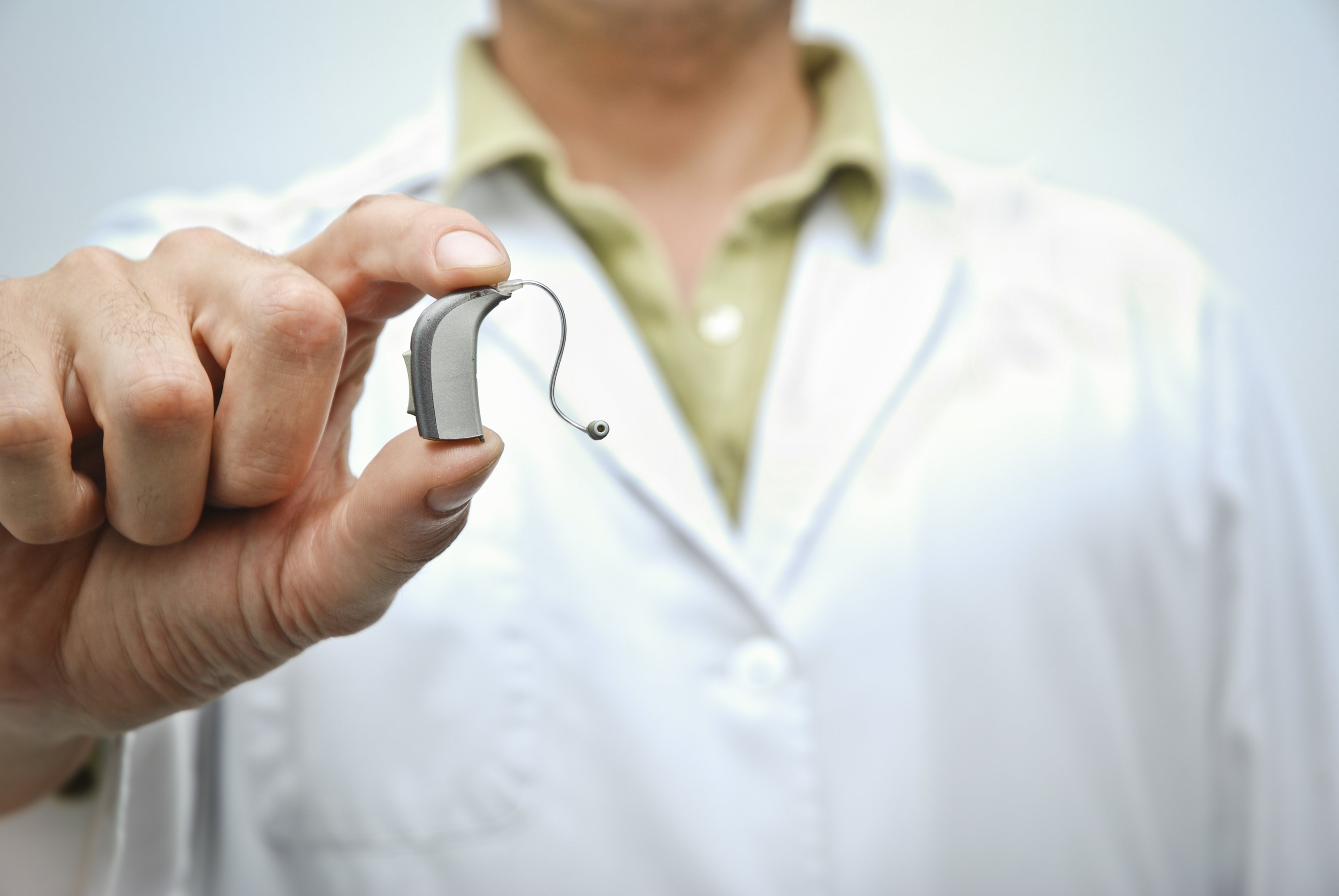 A doctor holding a hearing aid. | Photo: Getty Images