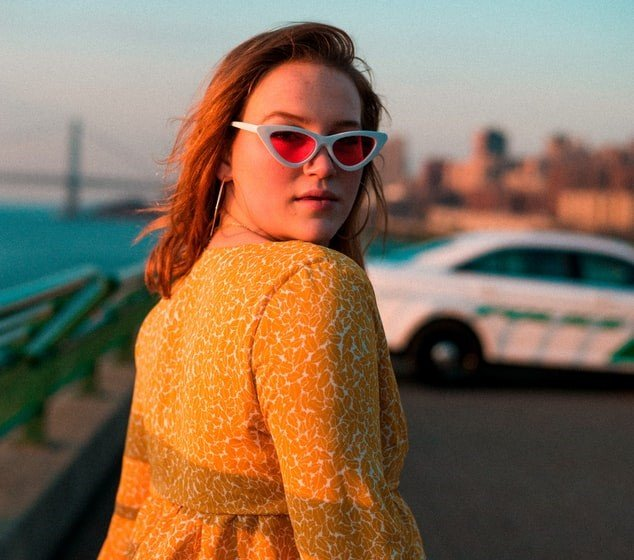 A model in red sunglasses coming out of an eatery | Photo: Unsplash