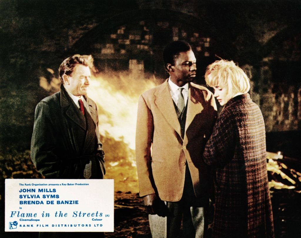 John Mills, Johnny Sekka and Sylvia Syms on a set of Flames In The Street circa 1961. | Photo: Getty Images