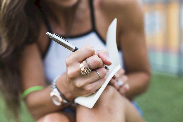 Une femme exhibant ses bagues tout en écrivant dans un carnet de notes. | Photo : Freepik