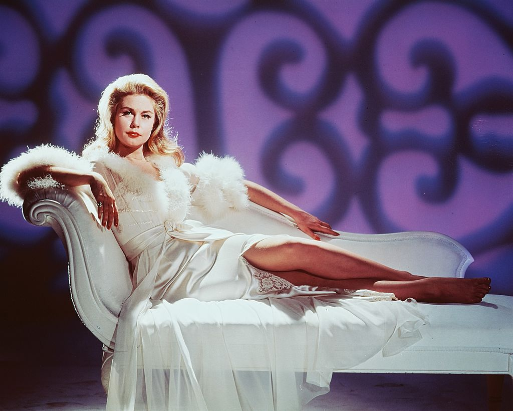 Actress Elizabeth Montgomery (1933-1995), reclining on a white chaise lounge, dressed up in a white gown trimmed with white fur, circa 1965 | Photo: Getty Images