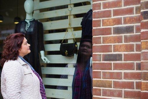 Frau schaut sich Auslade an im Schaufenster   Quelle: Shutterstock