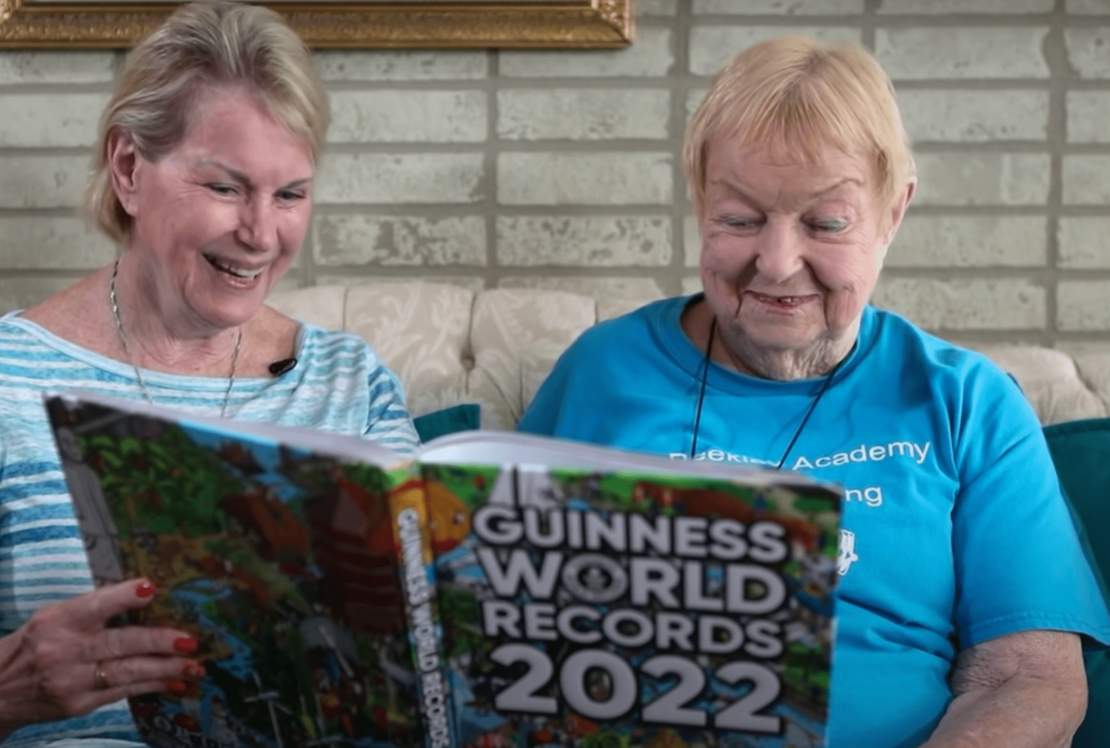 100-year-old woman and her daughter look through 2022 Guinness World Record book which honored her as a record holder for powerlifting   Photo: Youtube/Guinness World Records