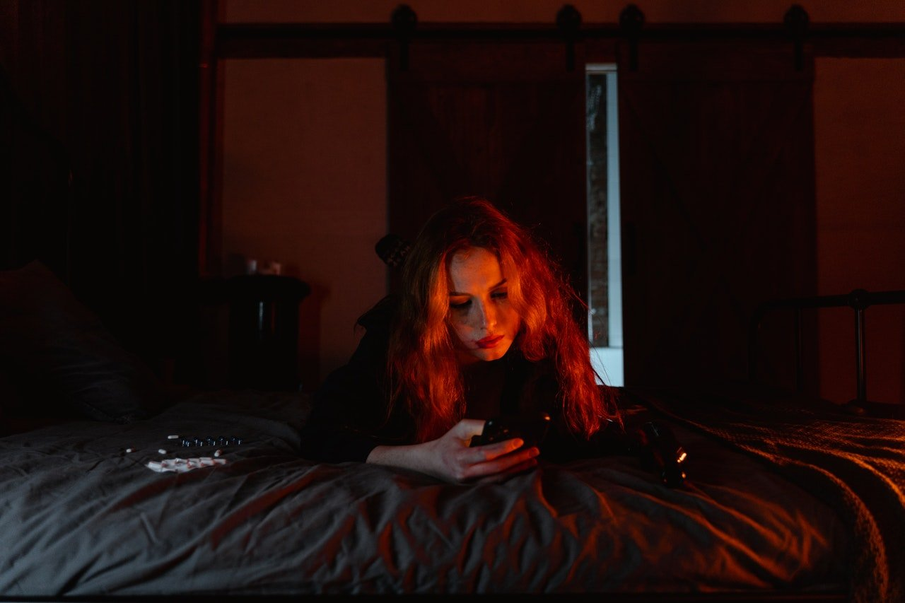 Woman using phone while lying on bed | Source: Pexels