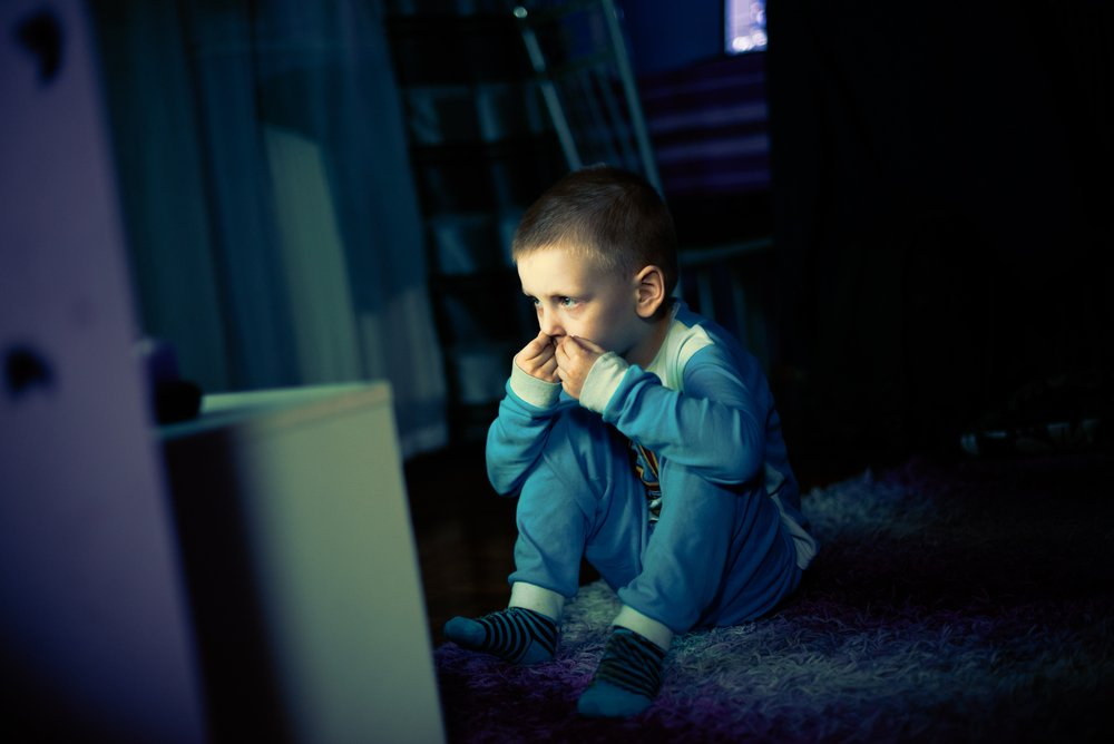 A sad little boy scared of the dark and watching the television. | Photo: Shteerstock.