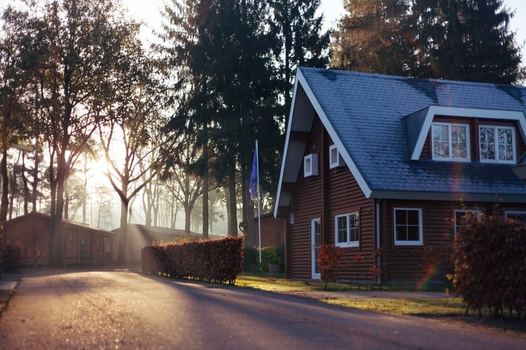 A photo of a brown house with a blue roof in a quiet neighborhood. | Photo: Unsplash.