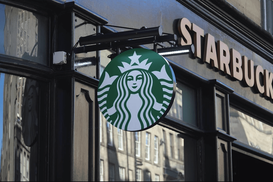 A Starbucks logo in front of one of the cafe | Photo: Pixabay