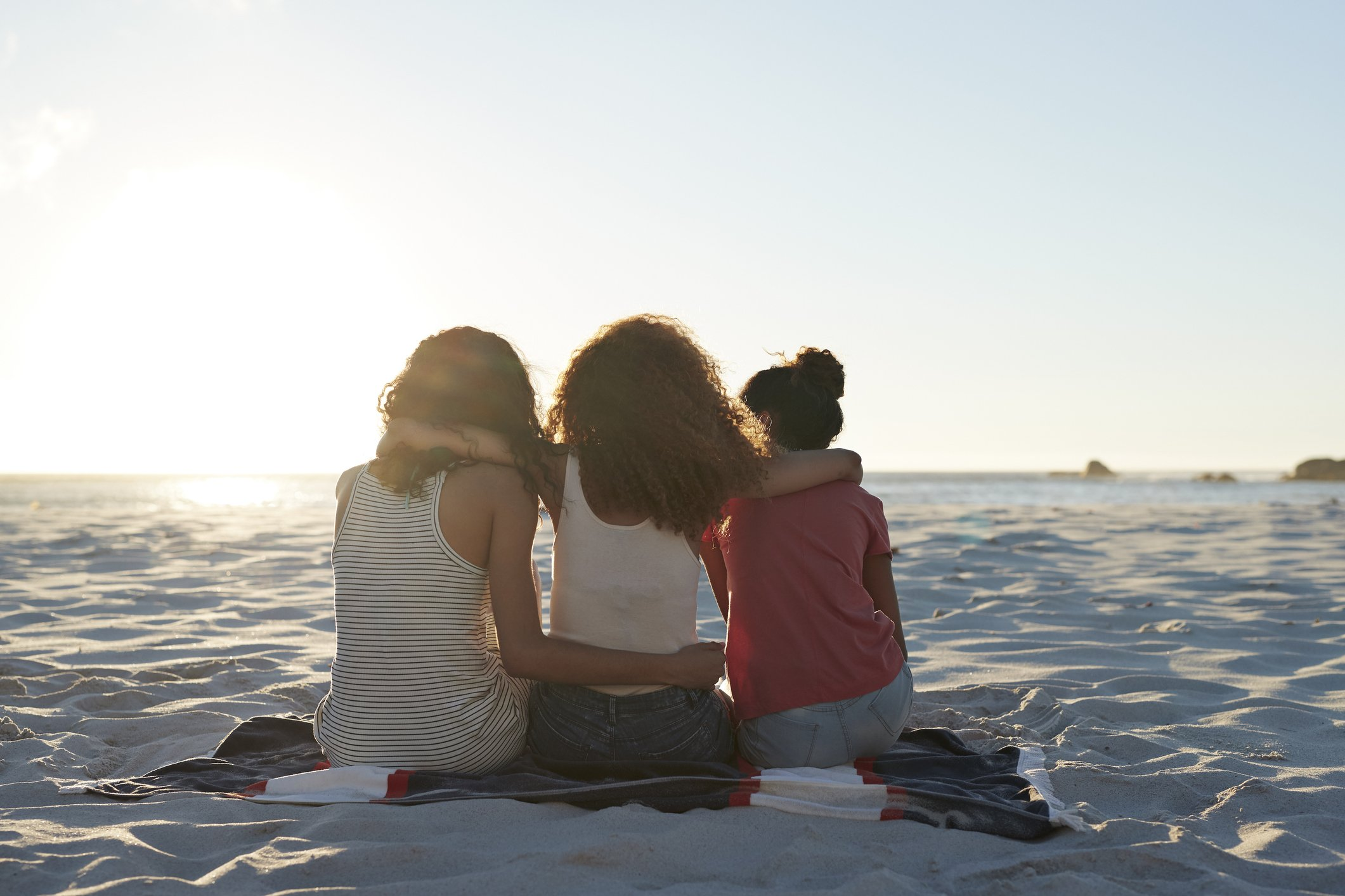 Rear view of three young women sitting on the beach. | Photo: Getty Images