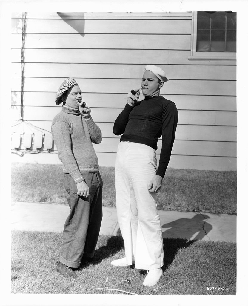 Cliff Edwards and William Haines holding pipes in a scene from the movie