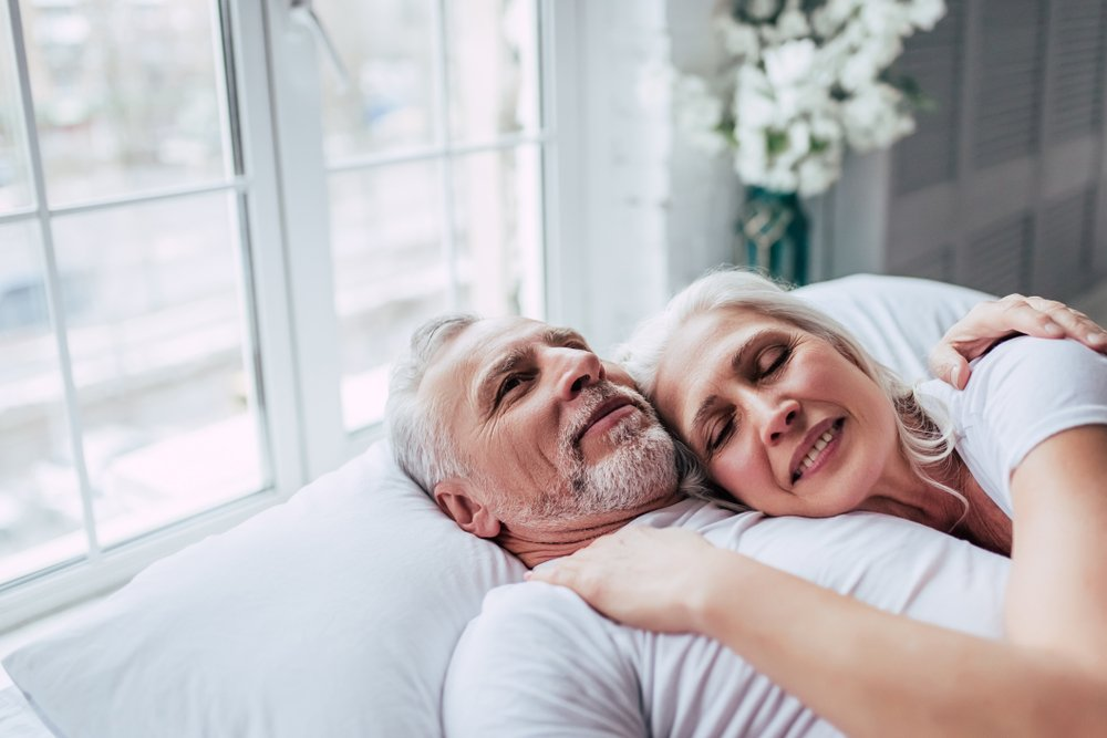 Elderly couple in bed together | Shutterstock