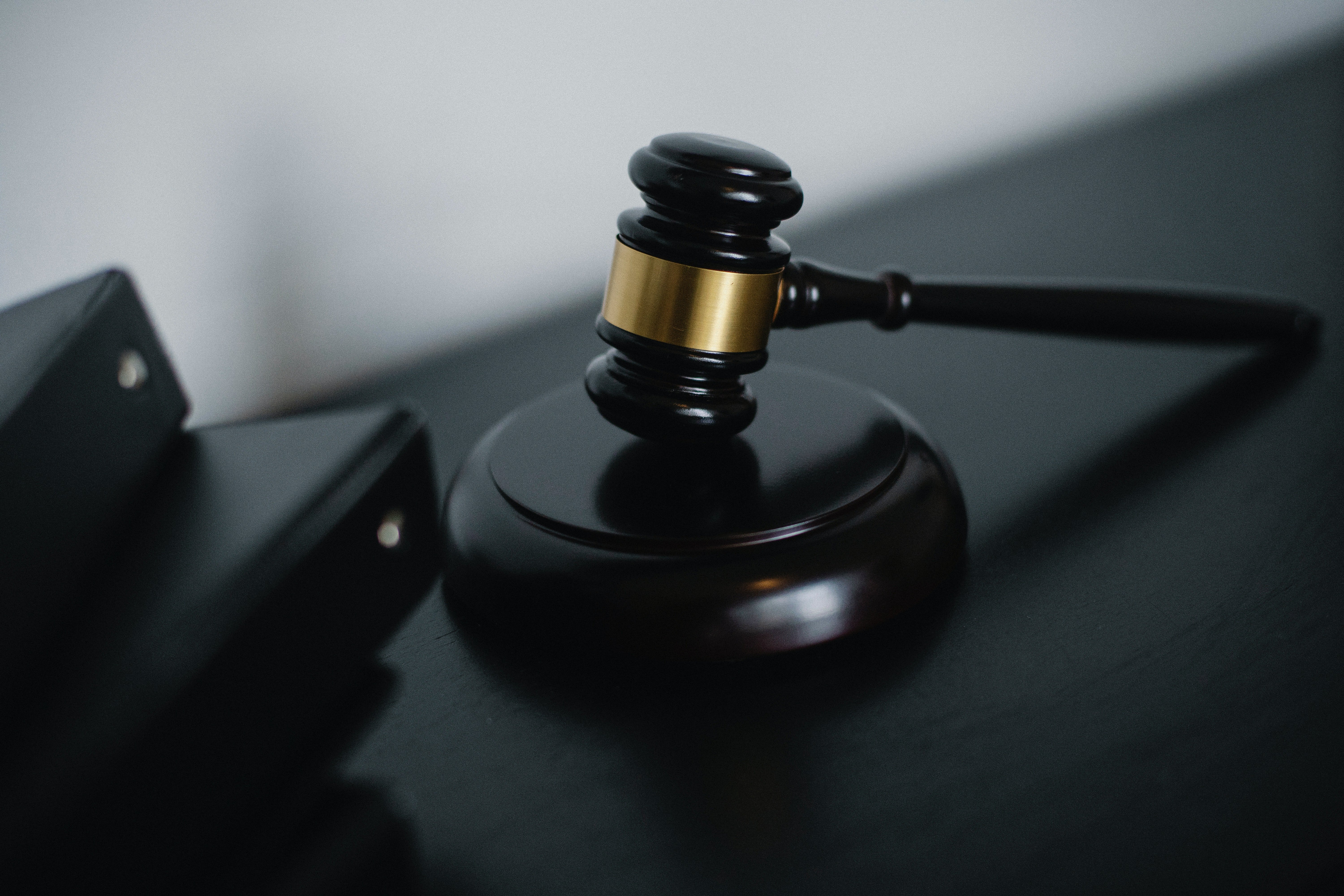 Pictured - A small judge gavel placed on the table near folders | Source: Pexels