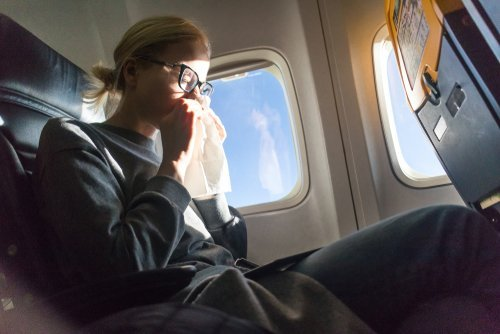 A young woman sneezing on an airplane. | Source: Shutterstock.