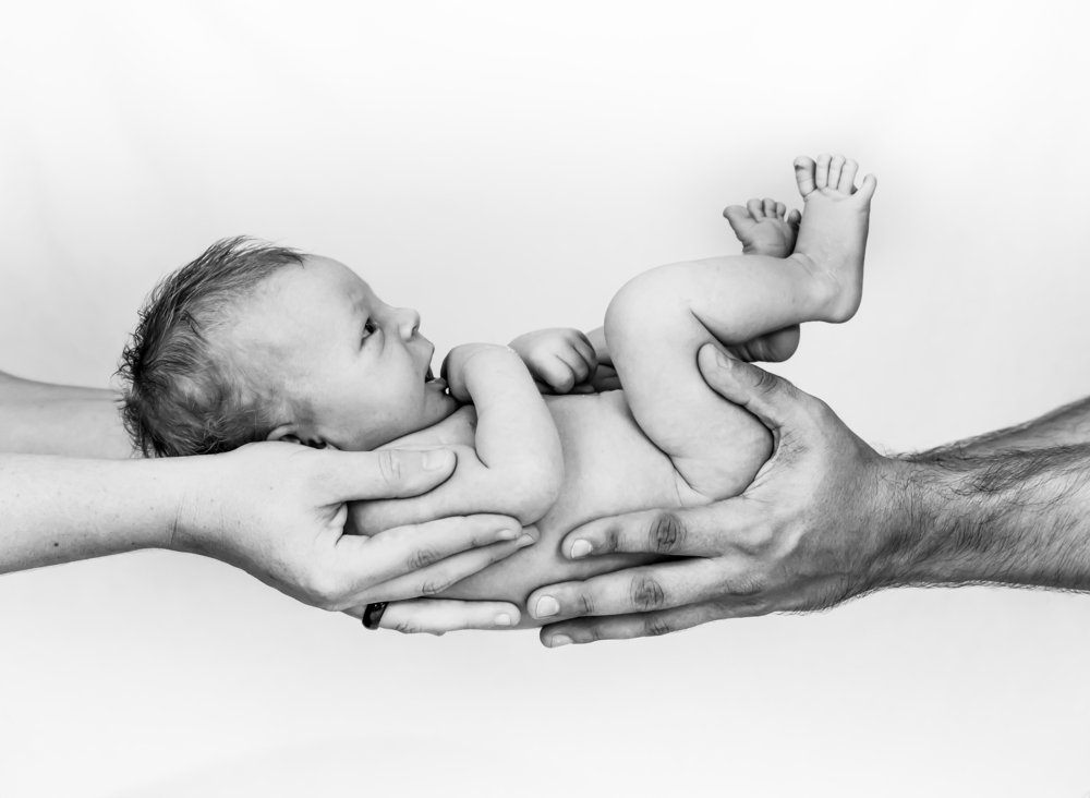 A mother and father's hands holding a newborn baby | Photo: Shutterstock/Simon Dannhauer