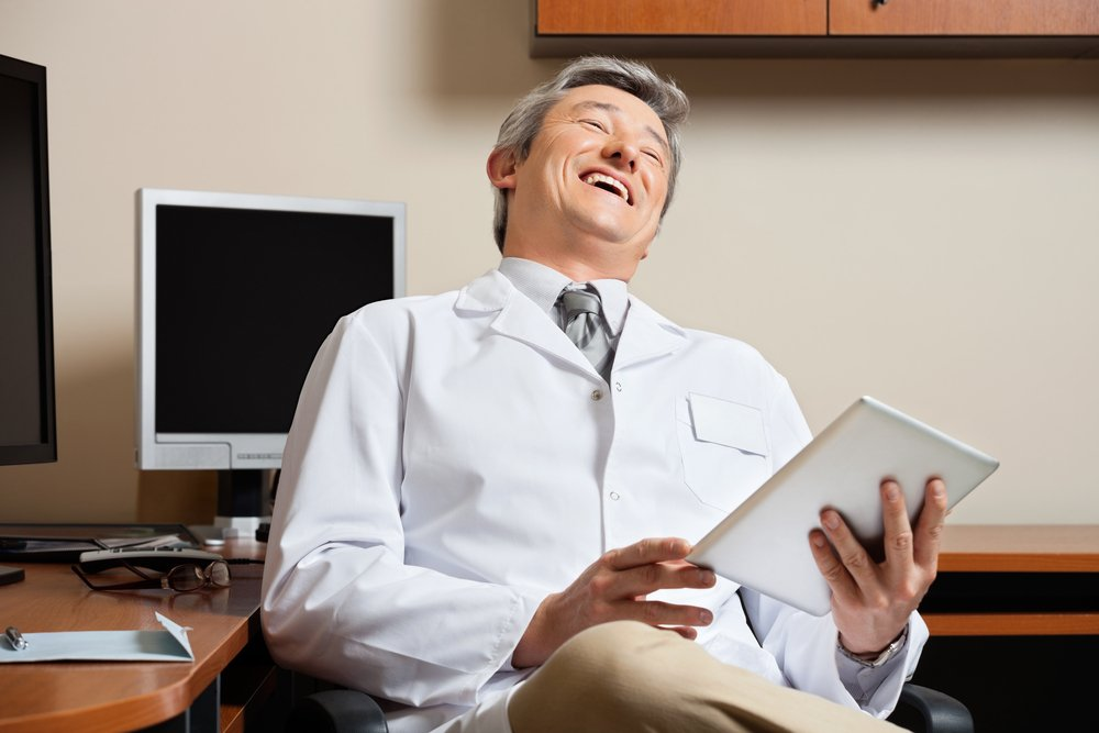 A photo of a doctor crossing his legs and laughing | Photo: Shutterstock