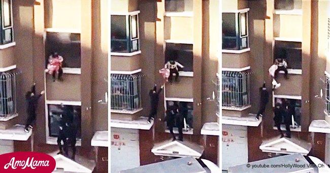 Bebé resbala peligrosamente de su mamá cuando escapaban de edificio en llamas en dramático video