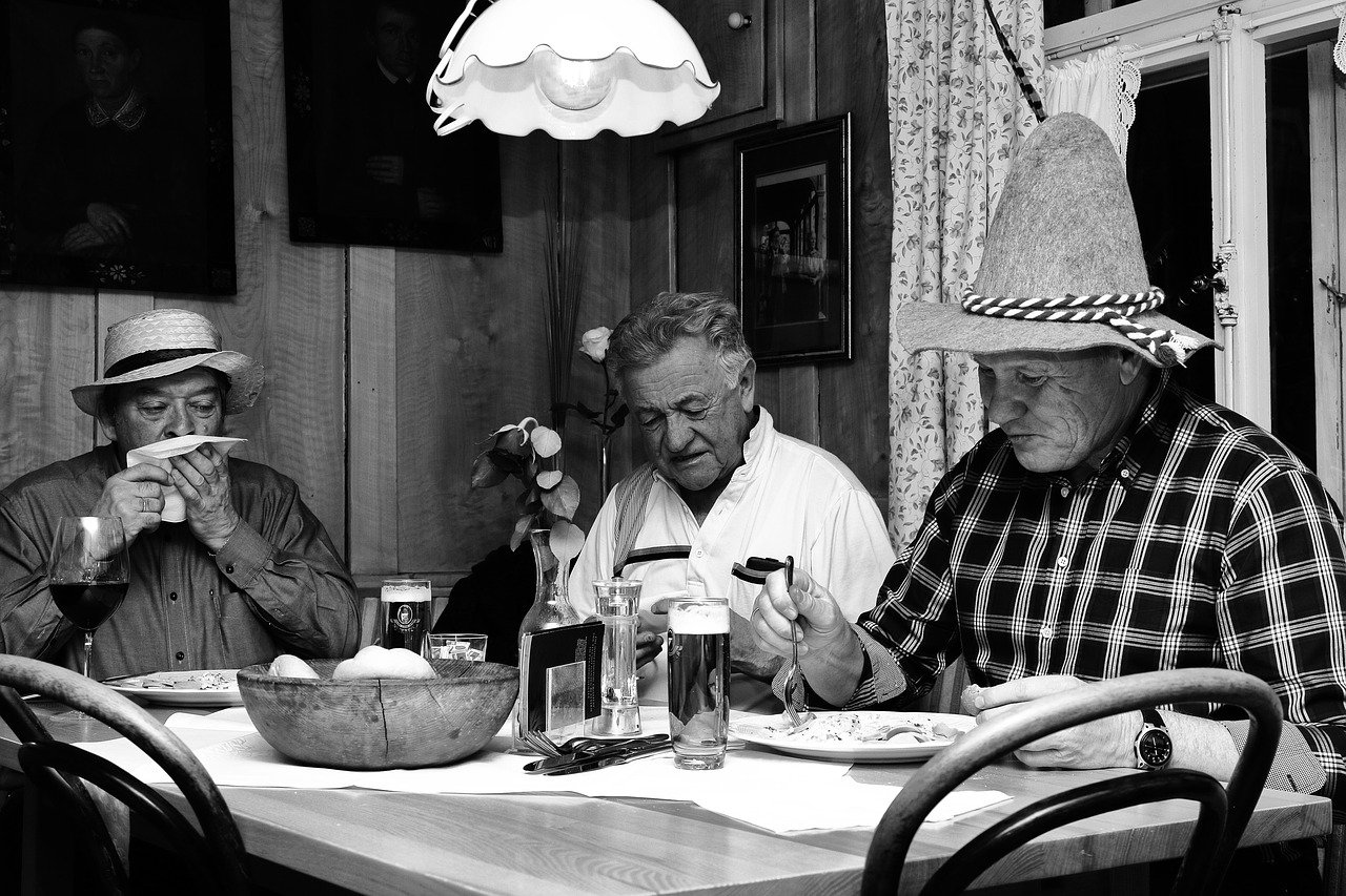 Three men having a hearty meal together in a black-and-white image | Photo: Pixabay/Kelly van de Ven