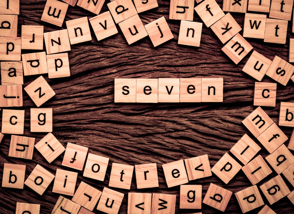 """A photo of wooden cubes for Puzzles that spells out """"Seven"""" 