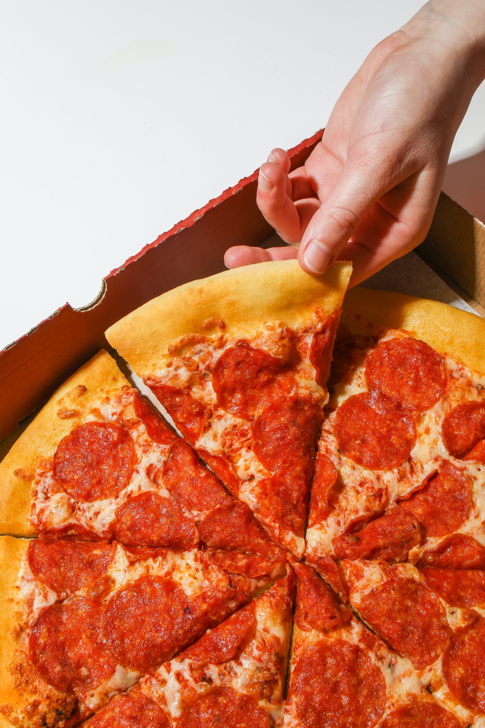 A person holding a slice of pizza.| Photo: Pexels/Polina Tankilevitch