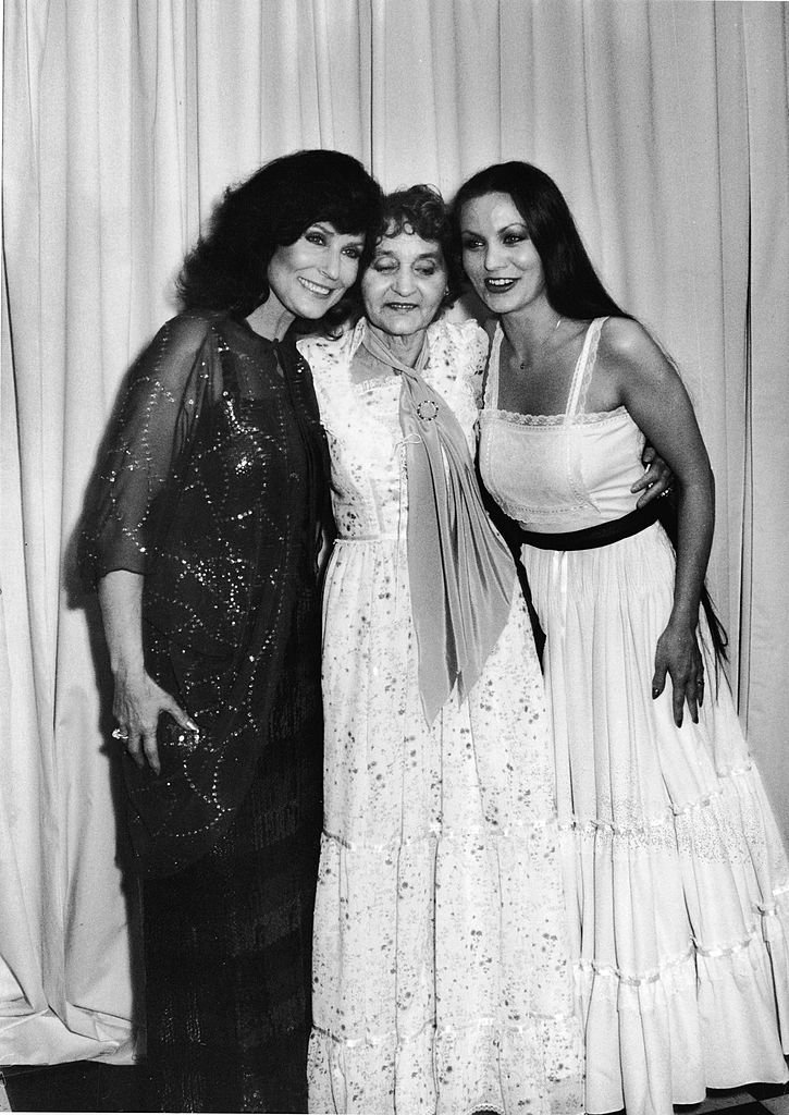American country music singer and guitarist Loretta Lynn (L) poses with her mother, Clara Webb Butcher (1907 - 1981), and her sister Crystal Gayle (R), also a county music singer, at the Country Music Awards, California, March 1, 1980. | Source: Getty Images