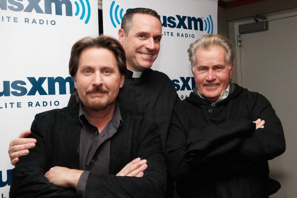 Emilio Estevez and Martin Sheen pose with Busted Halo host Father Dave (C) at SiriusXM Studio on October 7, 2011, in New York City. | Source: Getty Images.