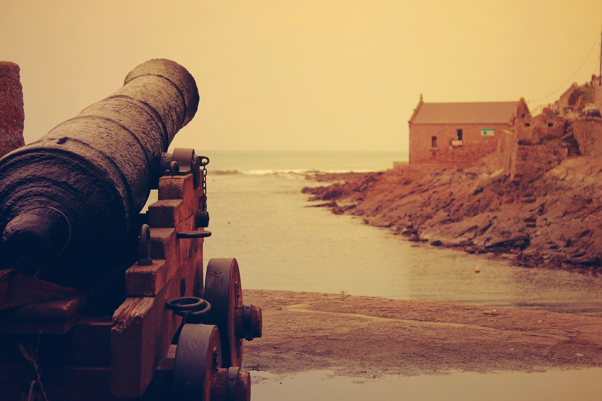 A cannon facing the seashore with a house in the distance | Photo: Pixabay/Free-Photos