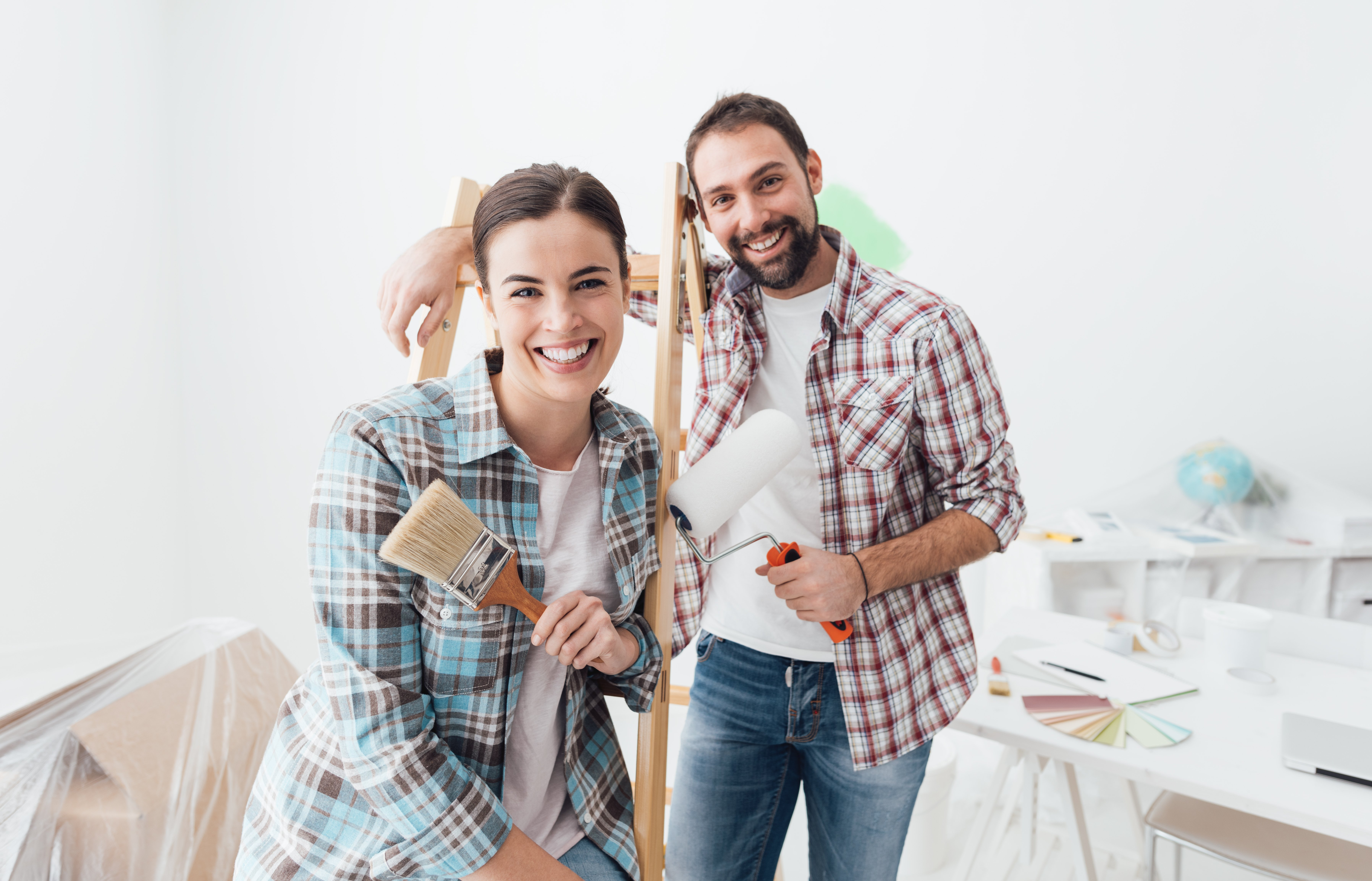 A man and woman painting their home. | Photo: Shutterstock