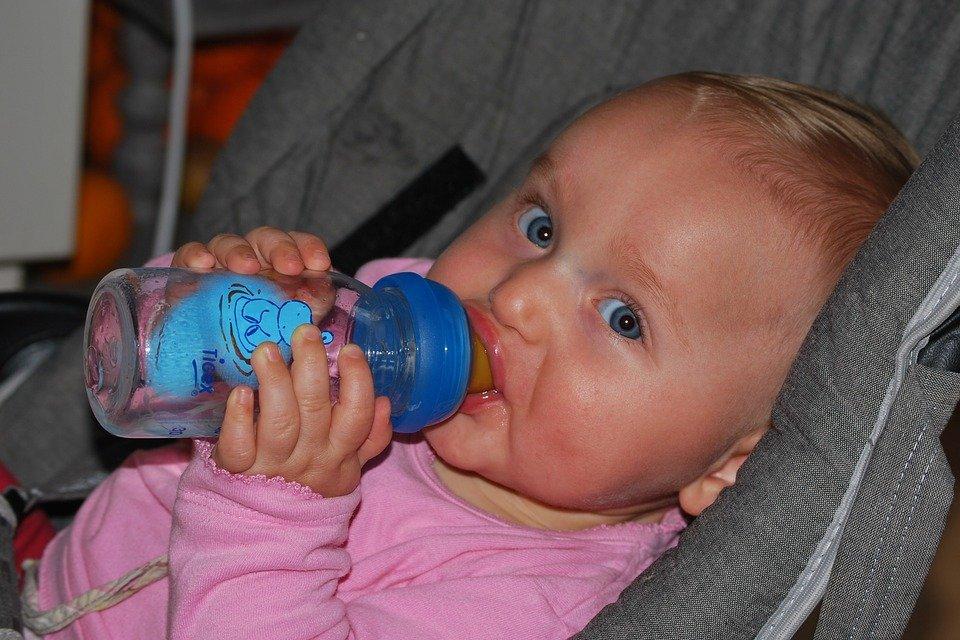 Baby mit Flasche guckt in die Kamera | Quelle: Pixabay