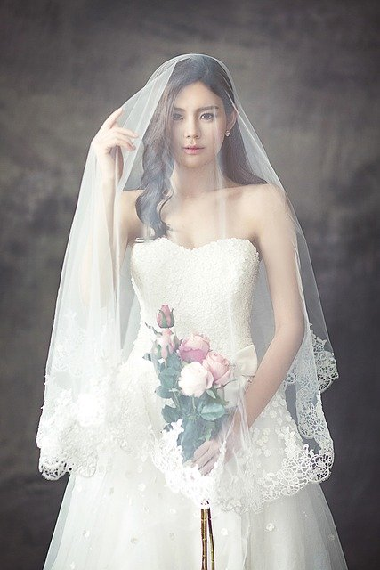 Woman wears white wedding dress with veil and bouquet | Photo: Pixabay