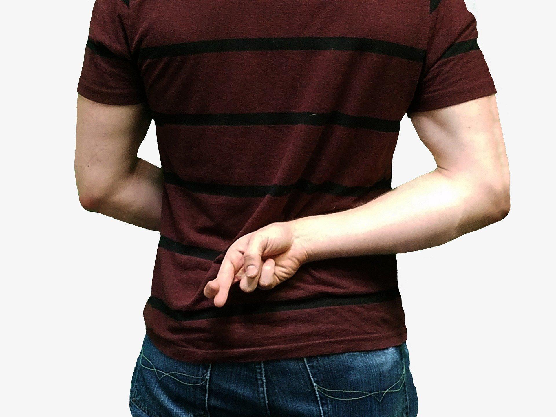Hombre con dedos cruzados tras la espalda. Fuente: Pixabay