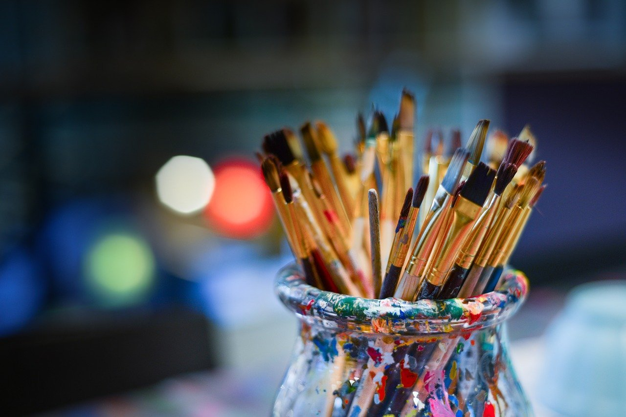 A bunch of different sized paint brushes sitting in a glass jar | Photo: Pixabay/Rudy and Peter Skitterians