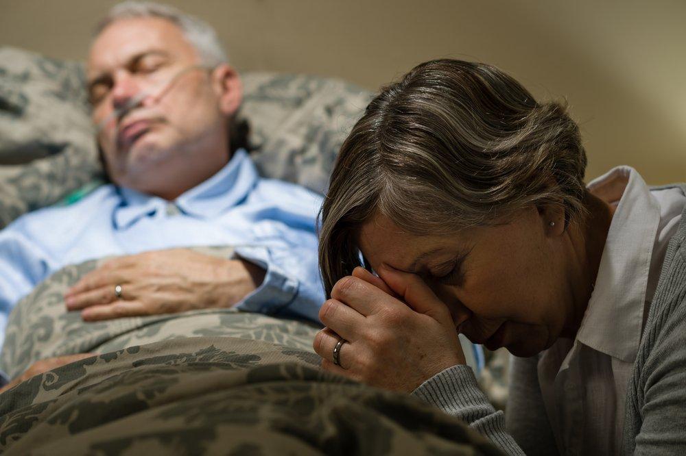 Une vieille femme au chevet de son mari. l Source: Shutterstock