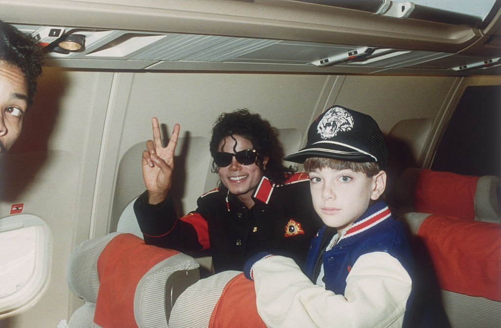 Michael Jackson on a tour plane with a young James Safechuck in July 1998. | Photo: Getty Images
