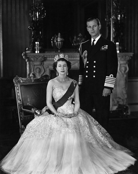 Queen Elizabeth II and Prince Phillip. She is seated and wearing a crown, he is standing in uniform. Undated photograph. | Photo: Getty Images