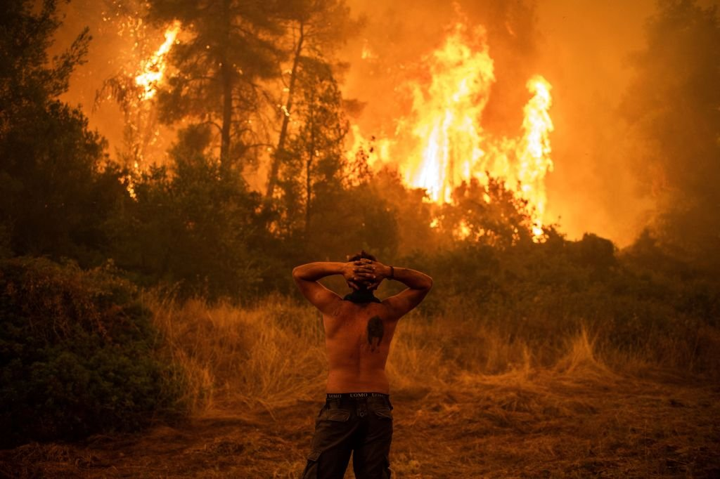 A man stared at the wildfire and it approached the village of Pefki on Evia (Euboea) island, Greece's second largest island. August 8, 2021 | Source: Getty Images