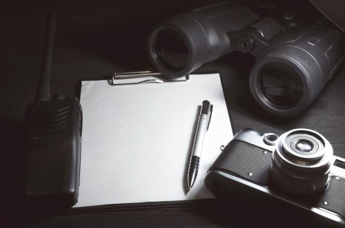 Blank page with copy space, pen, portable radio, binoculars and photo camera on a black spy agent table background. | Source: Shutterstock.