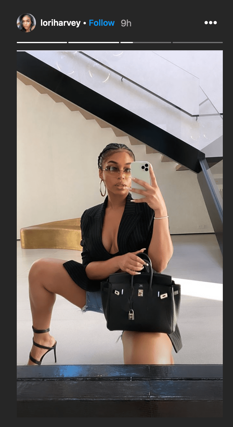 Lori Harvey showed of her designer handbag in a trendy denim shorts-and-blazer outfit | Source: Instagram.com/loriharvey