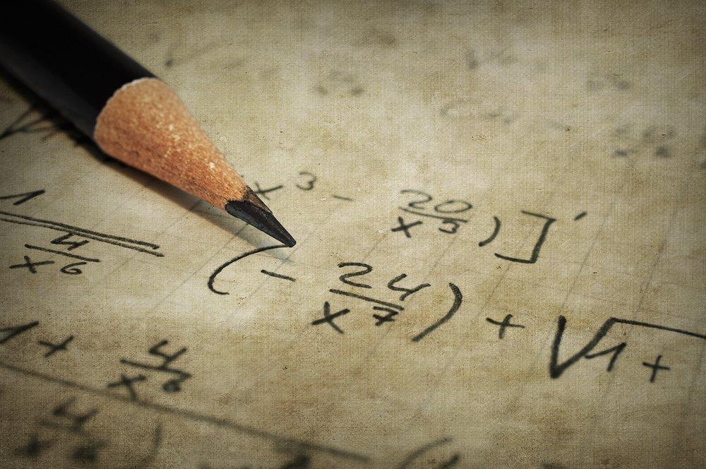 Feuille avec des équations mathématiques et un crayon. Source : Shutterstock