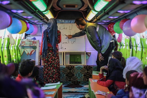 A Syrian teacher interacts with a Syrian child inside a bus which is converted into a classroom | Photo: Getty Images