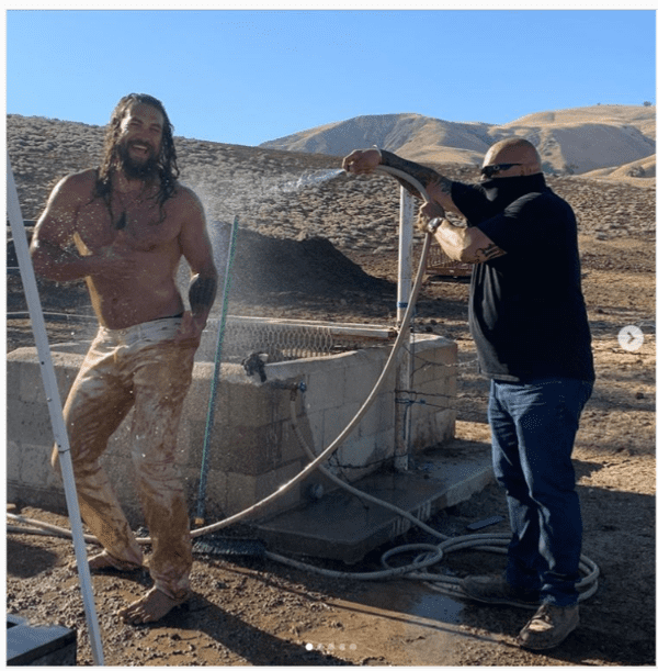 Jason Momoa being washed down with water after a dune buggy ride. | Photo: instagram.com/prideofgypsies