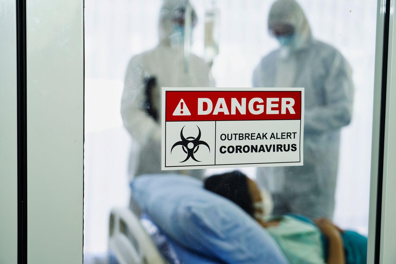 A coronavirus danger sign in front of a control area with a team of doctors in protective gear attending to an infected patient in a quarantined room   Photo: Shutterstock/Kobkit Chamchod