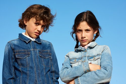 A boy and a girl distrustfully looking at the camera. | Source: Shutterstock.