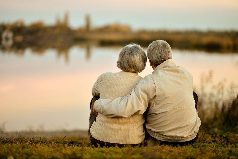 Couple heureux de personnes âgées assis au bord du lac pendant l'été, au coucher du soleil. | Source : Shutterstock