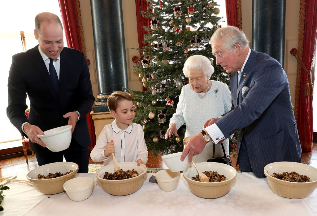 Prince William, Duke of Cambridge, Prince George, Queen Elizabeth II and Prince Charles, Prince of Wales prepare special Christmas puddings in the Music Room at Buckingham Palace, as part of the launch of The Royal British Legion's Together at Christmas initiative. | Photo: Getty Images