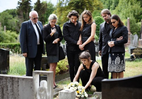 A family laying flowers on the grave of a beloved. | Source: Shutterstock.
