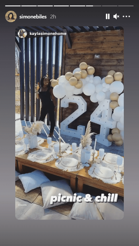 Simone Biles posing next to a balloon arrangement in front of a picnic table for her birthday party  Source: Instagram/simonebiles