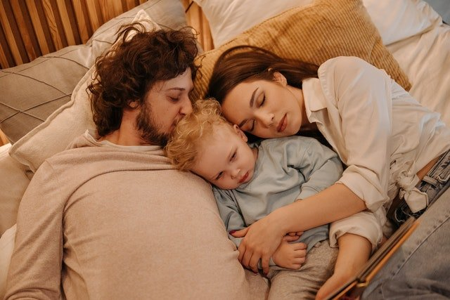 Family lying on bed| Source: Unsplash